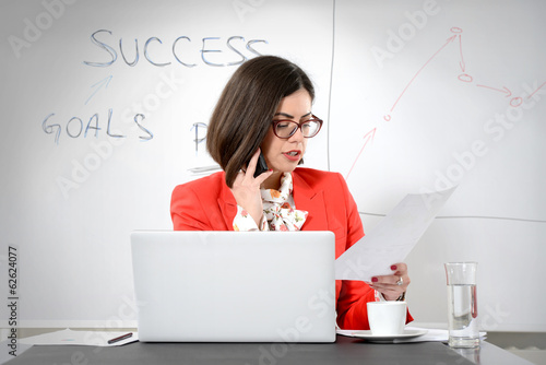 Young successful businesswoman multitasking