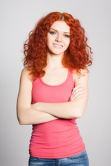 Joyful girl with red hair on gray wall