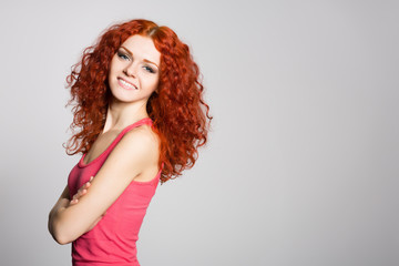 Smiling redhead girl on a background of gray wall