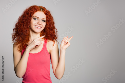 Smiling red haired girl is pointing fingers