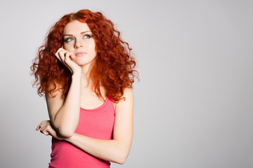 Portrait thinking red haired young woman