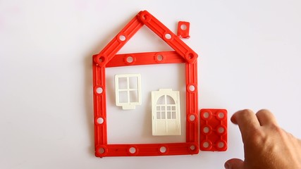 Human hand builds red house on white background.