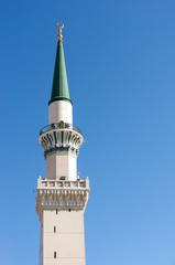 One of the towers at Nabawi Mosque against blue sky