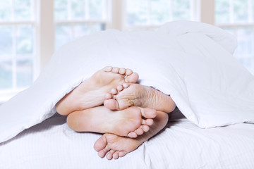 Close-up of couple feet cuddling 1