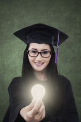 Female student giving bright light bulb