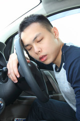 A young man falling asleep at the steering wheel