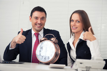 business couple showing thumbs up in the office
