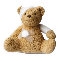 teddy bear with bandaged head on white background