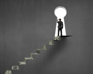 Businessman on top of money stairs with key hole
