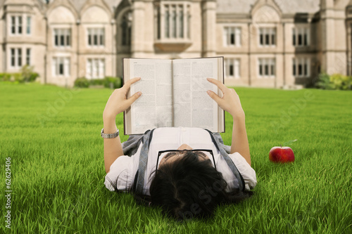 A student reading a book outdoor