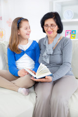 Grandmother and little girl reading a book  together at hom