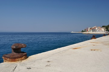 Mooring bollard in port with adriatic sea. Podgora, Croatia