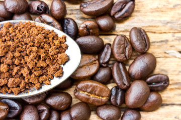 Coffee beans and ground coffee beans on a spoon.
