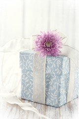 Blue floral gift box tied up with white ribbon