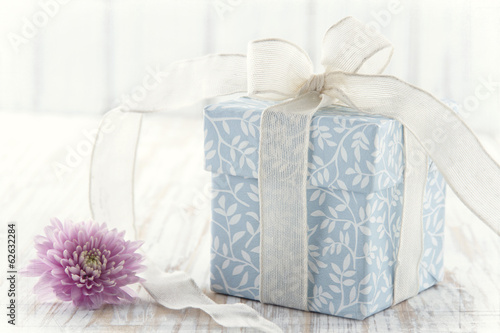 Gift box tied up with white ribbon and pink flower