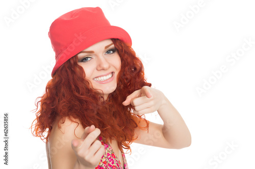Joyful girl in a red hat pointing at the camera