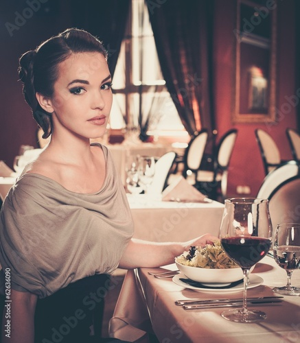 Young woman with glass of red wine in a restaurant