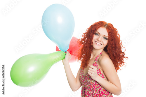 Happy red haired girl holding balloons