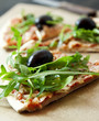 Slice of Pizza Margherita Closeup with Arugula and Olives