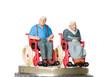 Altes Ehepaar im Rollstuhl auf einem Münzstapel