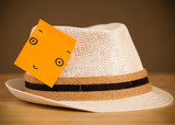 Post-it note with smiley face sticked on a hat