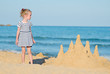 Little girl with sand castle on the beach.