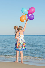 Little girl and her mother with balloons near the sea.