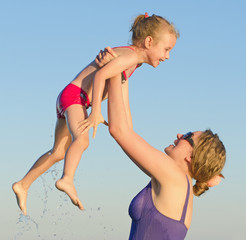 Mother and daughter having fun in the sea