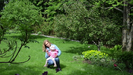 mother daughter blowing soap bubbles  garden the trees flowers