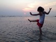 a little girl playing on the beach during sunset time