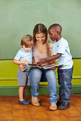 Erzieher und Kinder lesen Buch