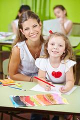 Erzieherin mit Mädchen beim Malen im Kindergarten