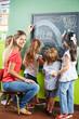 Kinder malen im Kindergarten an Tafel