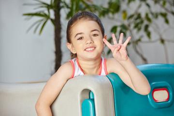 Mädchen zeigt vier Finger der Hand