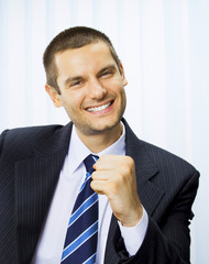 Happy successful gesturing businessman