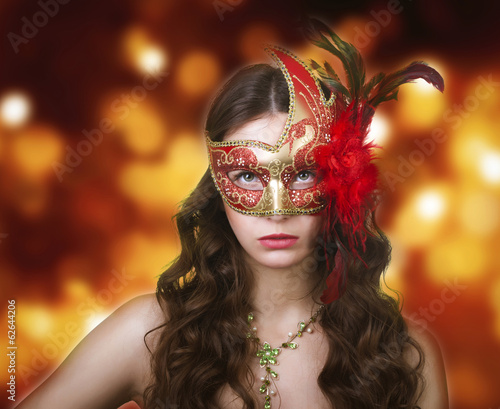 Woman in masquerade mask on a festive background.