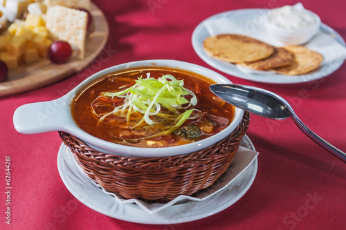 cabbage soup in a wicker plate crackers and sour cream