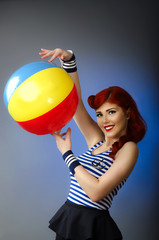 Portrait of a vintage pin up model playing with a beach ball