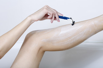 Beautiful woman is shaving her leg