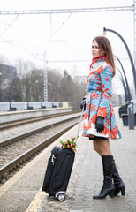 Woman waiting train with suitcase and flowers
