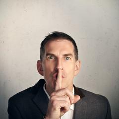 "Adult businessman saying ""Shh…"""