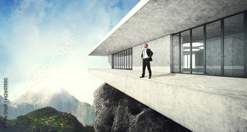 Successful man and his contemporary luxury house in mountains