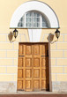 Wooden gate with arch in yellow classical facade. St.Petersburg
