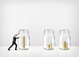 Man pushing glass jars with coins