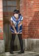 Asian schoolgirl in uniform outside school