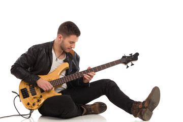 Male guitarist plays the bass guitar