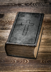 Old Bible on wooden table.