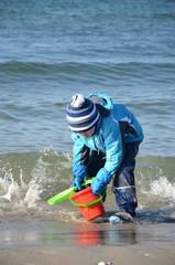 Kind spielt am Meer in wasserfester Kleigung