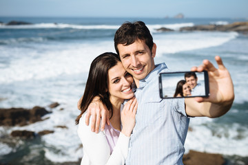 Couple on travel taking smartphone selfie photo