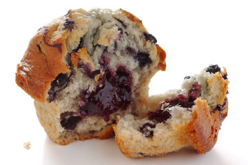 Broken blueberry muffin on white surface